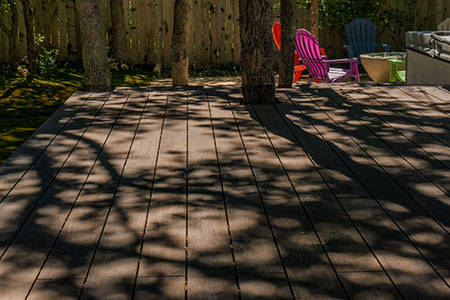 Built with Dasso XTR, a hardwood decking product made of fused bamboo, the deck cascades down to a stone patio with fire pit.